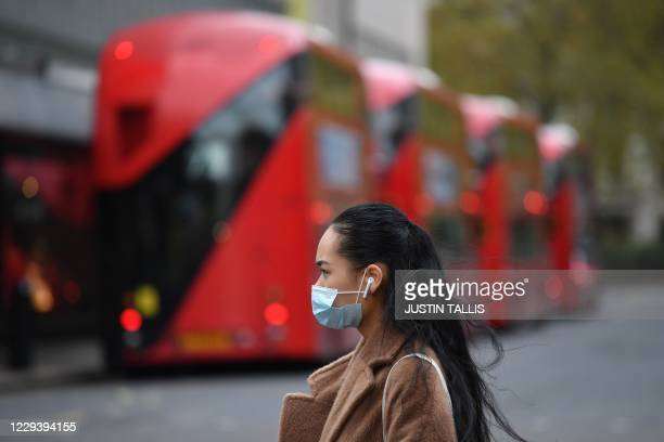 Pedestrian wearing a mask because of the coronavirus pandemic walks past parked buses in London on November 1, 2020 as England prepares to enter into...