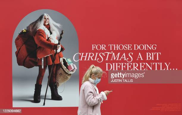 Pedestrian wearing a mask because of the coronavirus pandemic walks past a Christmas advertising sign in a shop window in London on November 1, 2020...