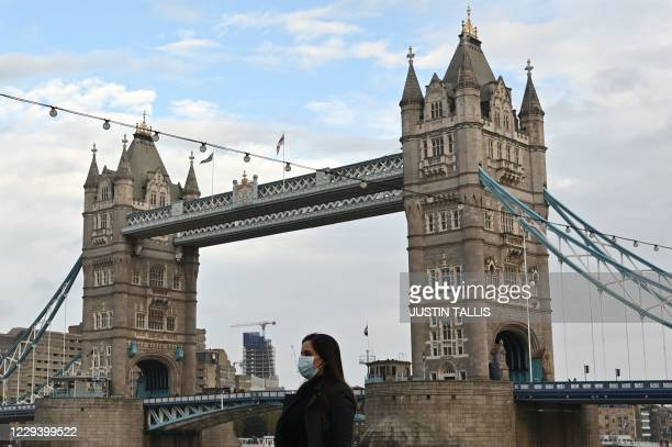 Pedestrian wearing a mask because of the coronavirus pandemic walks past Tower Bridge in London on November 1, 2020 as England prepares to enter into...