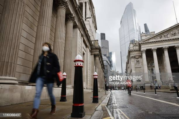 Pedestrian wearing a mask because of the coronavirus pandemic walks past the Bank of England in the City of London on December 11, 2020. - A Brexit...