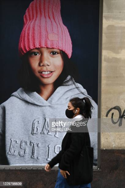 Pedestrian wearing a mask because of the novel coronavirus pandemic walks an advertisment for the clothing retailer Gap on Oxford Street in London on...