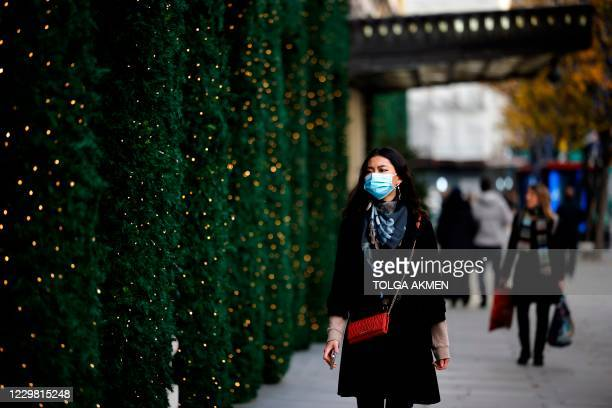 Pedestrian wearing a mask because of the novel coronavirus pandemic walks past a store front covered in Christmas decorations in central London on...