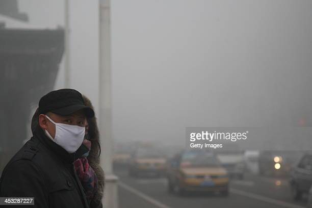 A pedestrian wearing a mask walks along a road as heavy smog engulfs the city on December 3 2013 in Harbin China Harbin Meteorological Bureau issued...