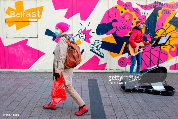 Pedestrian wearing a protective a face covering to combat the spread of the coronavirus, walks past a busker in Belfast city centre on Christmas Eve,...