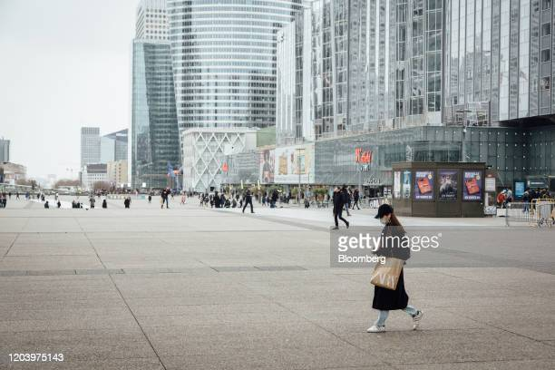 A pedestrian wearing a protective face mask carries a Zara fashion store carrier bag in the La Defense business district of Paris France on Friday...