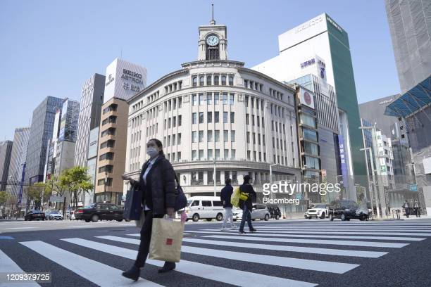 Pedestrian wearing a protective face mask crosses an intersection in Ginza shopping district in Tokyo, Japan, on April 8, 2020. Prime MinisterShinzo...