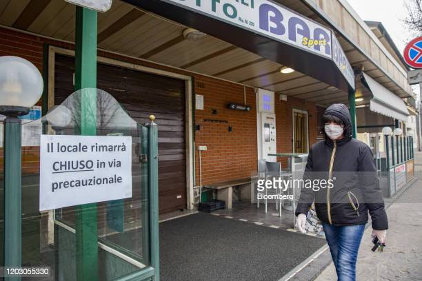 A pedestrian wearing a protective face mask passes a bar sign reading that it is closed for precautionary reasons in a yellow quarantine zone near...