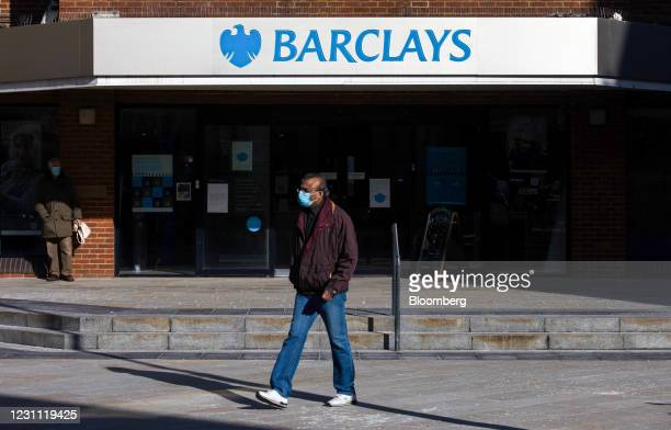 Pedestrian wearing a protective face mask passes a Barclays Bank Plc bank branch in Woking, U.K., on Friday, Feb. 12, 2021. The U.K. Economy grew at...