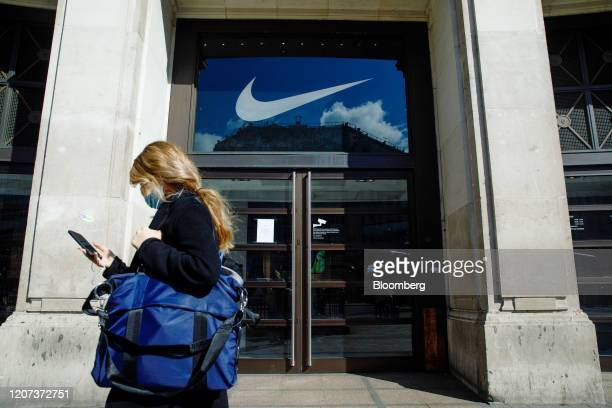 A pedestrian wearing a protective face mask passes a closed Nike Inc NikeTown store in London UK on Monday March 16 2020 Retail has become a...