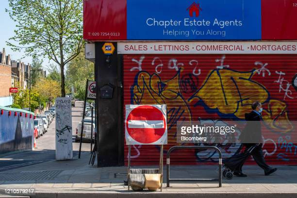 Pedestrian wearing a protective face mask passes a closed real estate agents in London, U.K., on Tuesday, April 21, 2020. U.K. Real estate agents...