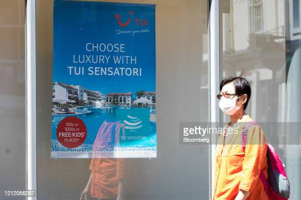 Pedestrian wearing a protective face mask passes a closed travel agency store, operated by Tui AG, in Ashford, U.K., on Wednesday, May 6, 2020....