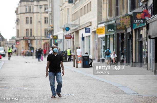Pedestrian wearing a protective face mask passes along a pedestrianised shopping precinct in Oxford, U.K., on Wednesday, May 27, 2020. The U.K....