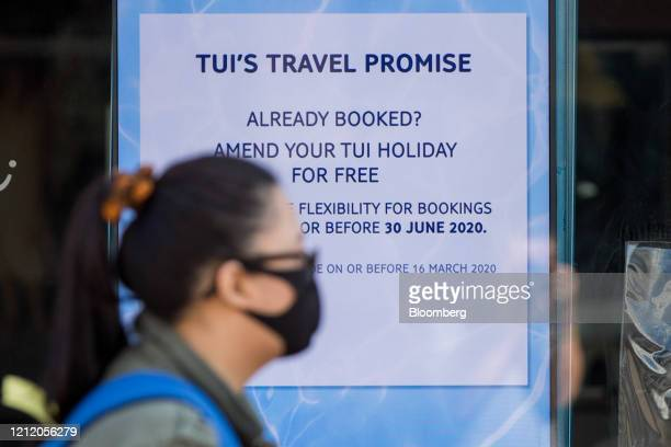 Pedestrian wearing a protective face mask passes an electronic advertising screen inside a closed travel agency store, operated by Tui AG, in Harlow,...