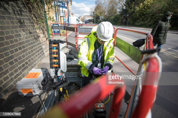 A pedestrian wearing a protective face mask passes an engineer for Openreach Ltd attaching fibre optics to a control unit in Chelmsford UK on Tuesday...