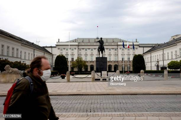 A pedestrian wearing a protective face mask passes the Presidential Palace in Krakowskie Przedmiescie street in Warsaw Poland on Wednesday April 29...