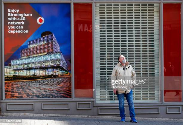 Pedestrian, wearing a protective face mask, stands outside a Vodafone Group Plc store near a advertising message about their 4G network in...