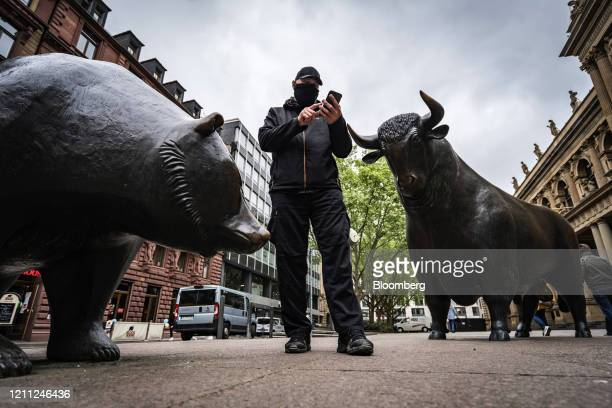 Pedestrian wearing a protective face mask uses a smartphone between a bear and a bull statue outside the Frankfurt Stock Exchange, operated by...