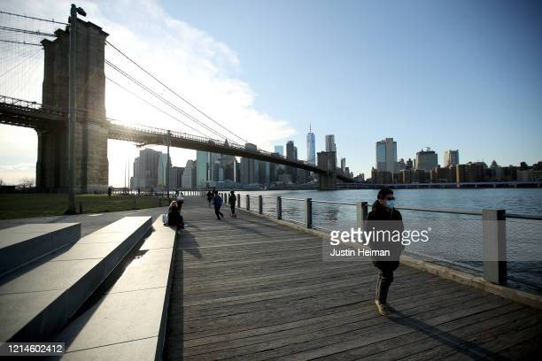 Pedestrian, wearing a protective face mask walk the pier on March 24, 2020 in the Dumbo neighborhood of the Brooklyn borough of New York City. New...