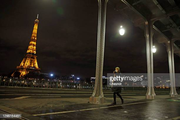 Pedestrian wearing a protective face mask walks near the illuminated Eiffel Tower after the curfew which starts at 6 p.m. During the coronavirus...