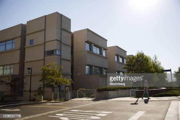 Pedestrian wearing a protective face mask walks outside Amgen Inc. Headquarters in Thousand Oaks, California, U.S., on Thursday, Aug. 27, 2020. Amgen...