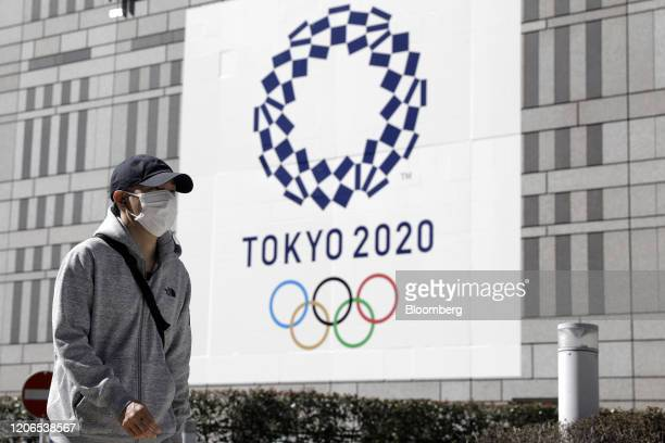 Pedestrian wearing a protective face mask walks past a banner featuring the emblem for the Tokyo 2020 Olympic Games in Tokyo, Japan, on Wednesday,...