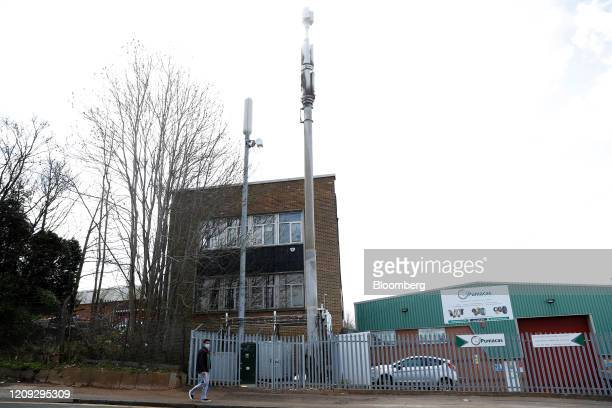 A pedestrian wearing a protective face mask walks past a firedamaged telecom tower reported in local media as being a 5G network mast on the EE...