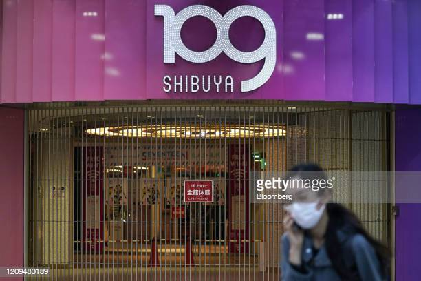 A pedestrian wearing a protective face mask walks past the 109 Shibuya fashion building temporary closed due to the coronavirus outbreak in the...
