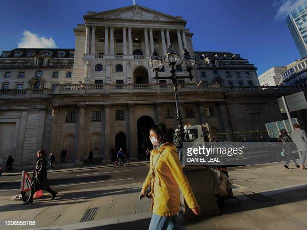 Pedestrian, wearing a protective face mask, walks past the Bank of England in the City of London on March 11 as Britain braces itself for an increase...