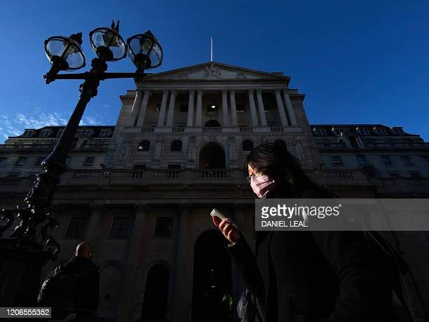 TOPSHOT A pedestrian wearing a protective face mask walks past the Bank of England in the City of London on March 11 as Britain braces itself for an...