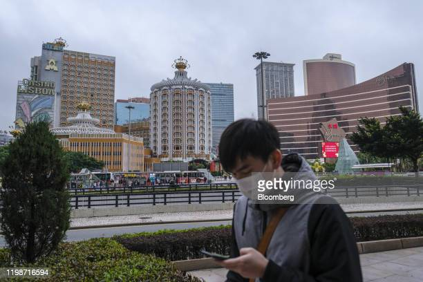 Pedestrian wearing a protective face mask walks past the Casino Lisboa, operated by SJM Holdings Ltd., left, and Wynn Casino resort, operated by Wynn...