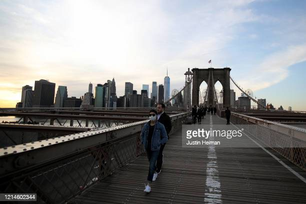 Pedestrian, wearing a protective face mask walks the Brooklyn Bridge on March 24, 2020 in the Dumbo neighborhood of the Brooklyn borough of New York...