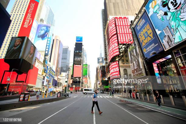 A pedestrian wearing a protective face mask walks through Times Square during the coronavirus pandemic on April 25 2020 in New York City COVID19 has...