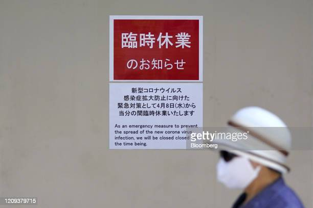 A pedestrian wearing a protective mask and a hat walks past a temporary closure sign displayed at Ginza Six mixeduse complex in Ginza shopping...