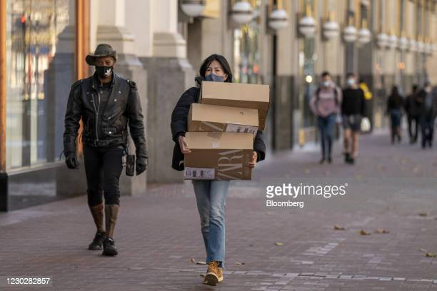 Pedestrian wearing a protective mask carries boxes in San Francisco, California, U.S., on Wednesday, Dec. 23, 2020. Bloomberg is scheduled to release...