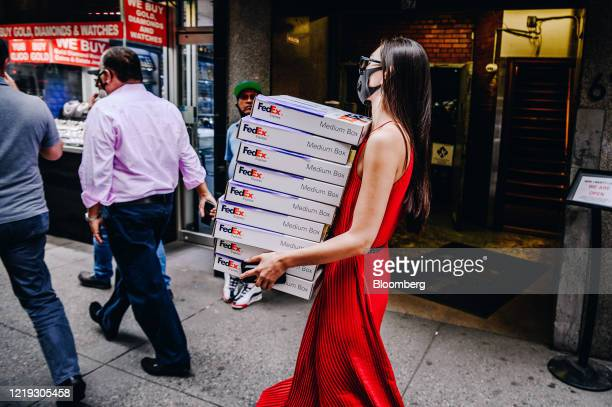 Pedestrian wearing a protective mask carries FedEx Corp. Boxes in the Diamond District of New York, U.S., on Wednesday, June 10, 2020. New York...
