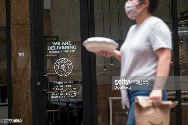 A pedestrian wearing a protective mask carries food outside a Chipotle Mexican Grill Inc restaurant in San Francisco California US on Monday July 20...