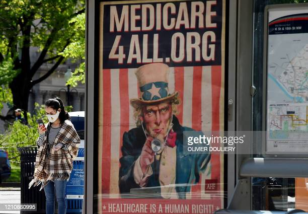 A pedestrian wearing a protective mask checks her phone near a Medicare for All bus stop billboard in Washington DC on April 22 2020