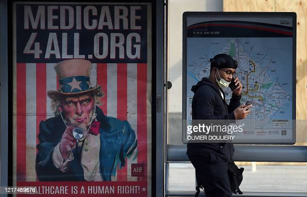 A pedestrian wearing a protective mask checks her phone near as she walks by a Medicare for All bus stop billboard in Washington DC on June 3 2020...