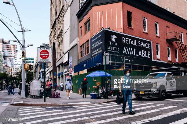 """Pedestrian wearing a protective mask crosses a street in front of a building displaying Thor Equities LLC signage that reads """"Retail Space Available""""..."""