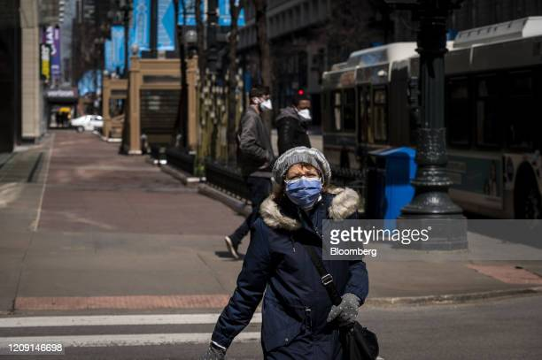 A pedestrian wearing a protective mask crosses the street in Chicago Illinois US on Friday April 3 2020 The world's workers are reeling from the...