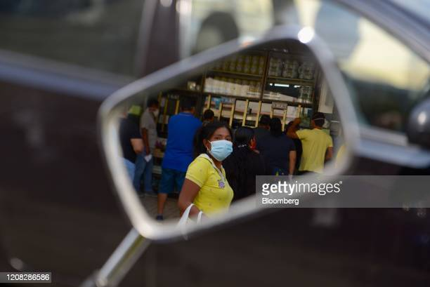 A pedestrian wearing a protective mask is reflected in the side mirror of a vehicle in Guayaquil Ecuador on Thursday March 26 2020 Nowhere has the...