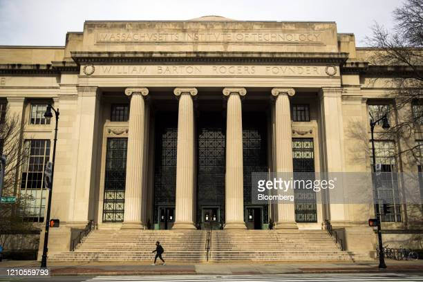 A pedestrian wearing a protective mask passes Building 7 on the Massachusetts Institute of Technology campus in Cambridge Massachusetts US on Monday...