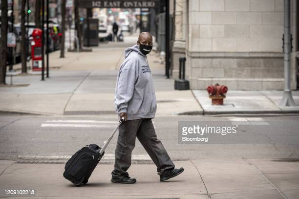Pedestrian wearing a protective mask walks along a street in Chicago, Illinois, U.S., on Friday, April 3, 2020. The world's workers are reeling from...
