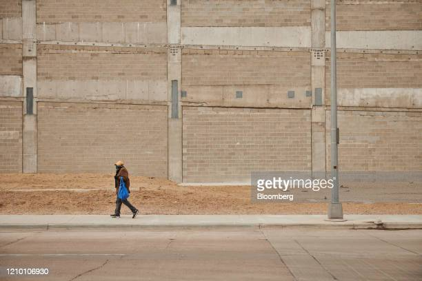 A pedestrian wearing a protective mask walks along a street in downtown Sioux Falls South Dakota US on Wednesday April 15 2020 South Dakota Governor...