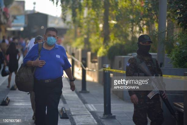 A pedestrian wearing a protective mask walks by a soldier patrolling the streets as State of Exception was declared on March 18 2020 in San Salvador...