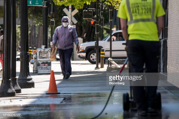 Pedestrian wearing a protective mask walks on 10th Street in Sacramento, California, U.S., on Tuesday, April 14, 2020. Some of the nation's most...