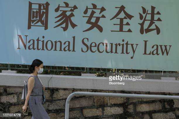 Pedestrian wearing a protective mask walks past a government-sponsored advertisement promoting a new national security law China plans to enact in...