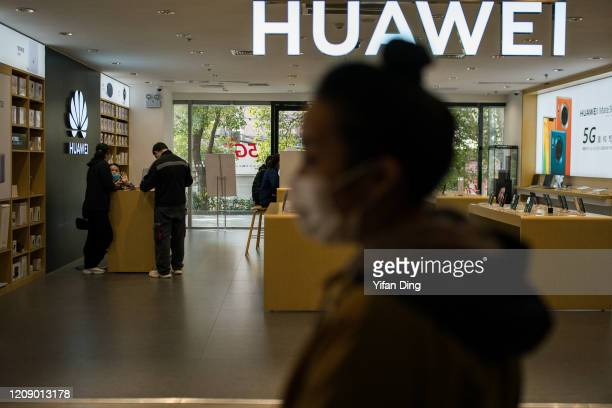 A pedestrian wearing a protective mask walks past a Huawei store in a shopping mall on February 27 2020 in Shanghai China China is gradually getting...