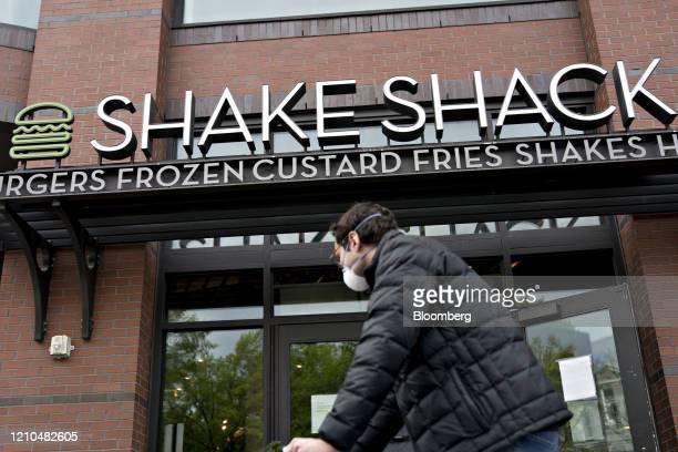 Pedestrian wearing a protective mask walks past a Shake Shack restaurant in Washington, D.C., U.S., on Monday, April 20, 2020. Shake Shack Inc. Will...