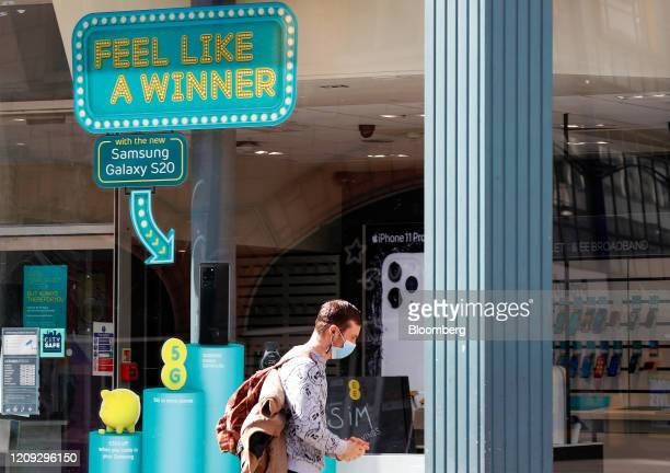 Pedestrian, wearing a protective mask, walks past an advertisement for 5G network services at an EE store, operated by BT Group Plc, in Birmingham,...